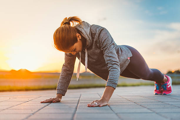 determined woman doing push ups - push up stock photos and pictures