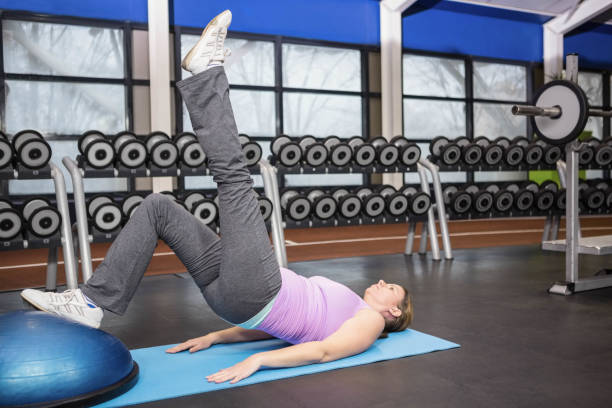 Determined woman exercising with bosu ball stock photo