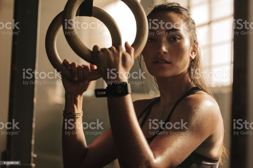 Determined woman exercising with gymnastic rings stock photo