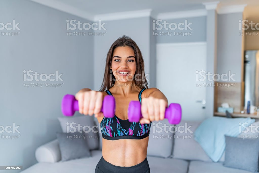 determined-woman-losing-weight-at-home-and-exercising-with-dumbbells-picture-id1068782662