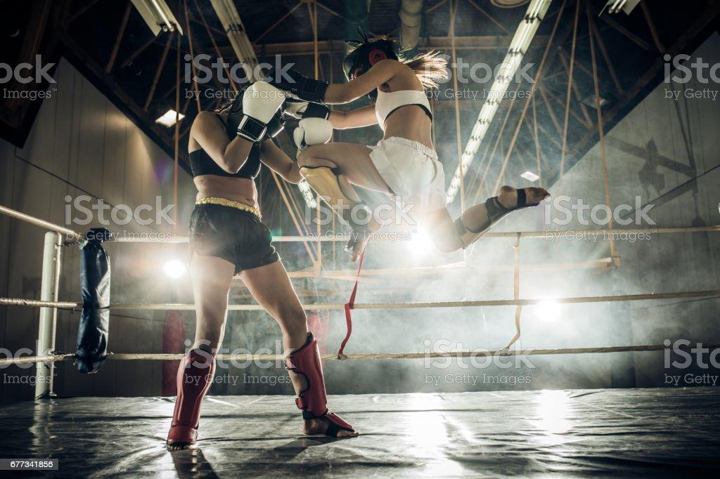 Mulher decidida, fazendo um movimento de voo e chutar seu adversário com um joelho. - foto de acervo