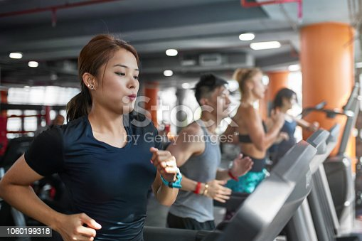 istock Determined woman running on treadmill in gym 1060199318