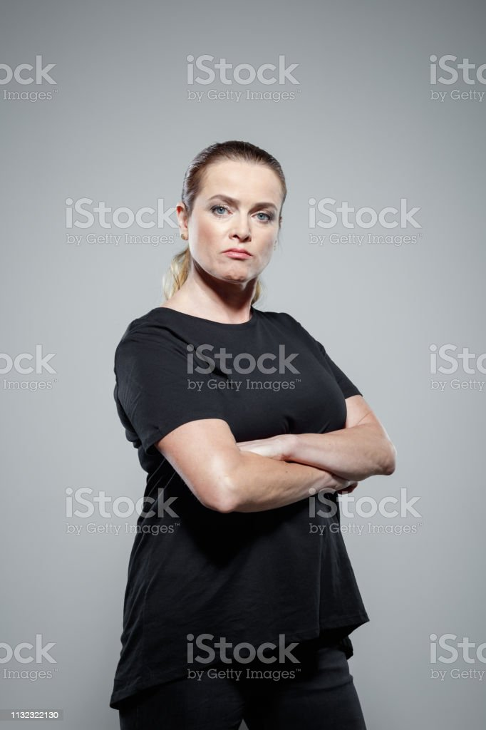 Determined woman supporting Me Too movement Portrait of determined mature woman wearing black clothes. Brave female is standing arms crossed against gray background. She is supporting Me Too movement. 40-44 Years Stock Photo