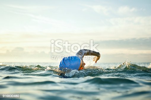 Determined woman swimming in sea. Mature female is enjoying water sport during sunset. She is representing healthy lifestyle.