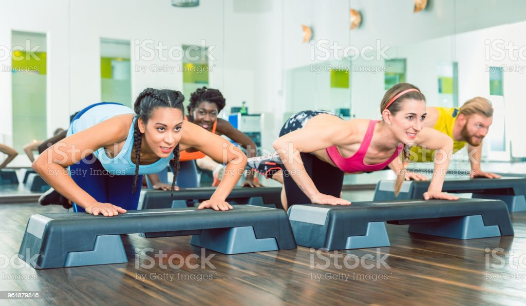 Determined women exercising push-ups on aerobic stepper platforms royalty-free stock photo