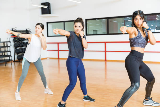 Determined Women Punching The Air In Gym stock photo