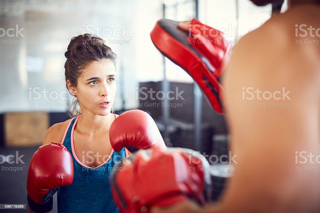 Determined young female fit boxer practicing in gym stock photo