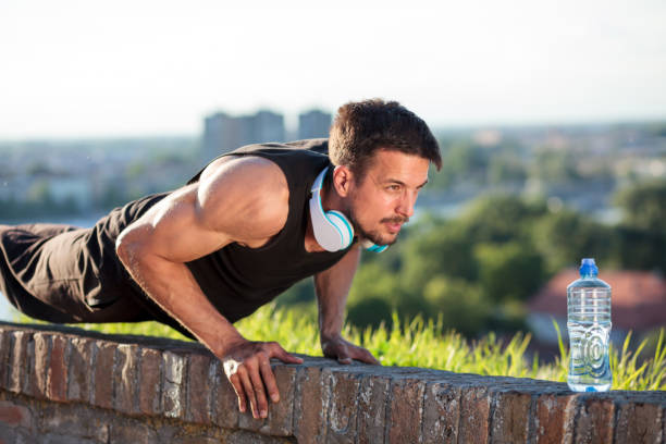 determined young man doing push-ups - man city exercise abs foto e immagini stock