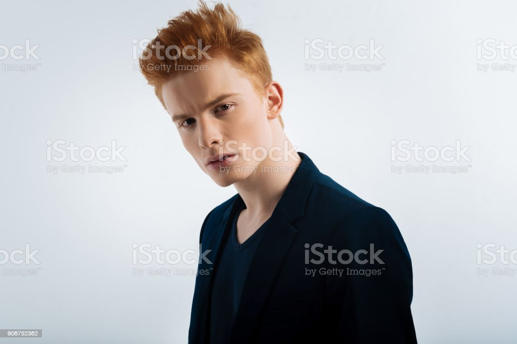 Determined young man having a stylish haircut stock photo