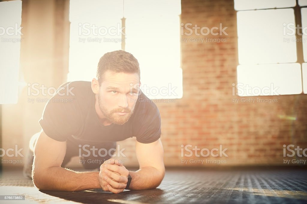 Determined young man performing plank position in gym stock photo