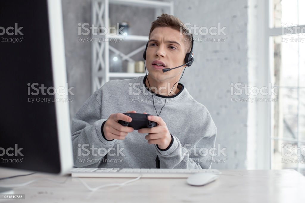 Determined young man playing computer games stock photo