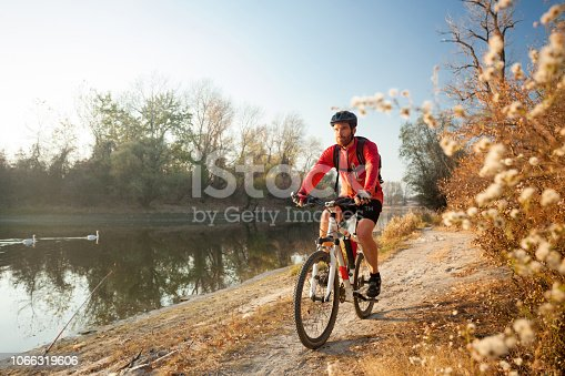 Determined young man riding mountain bike on a footpath along the lake or river on a clear autumn day. Healthy and active lifestyle concept