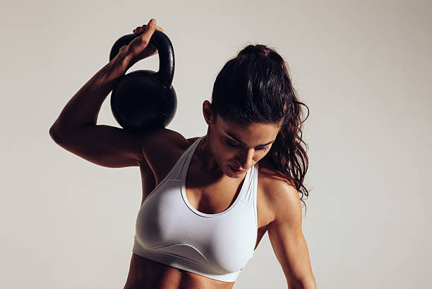 Determined young woman doing gym workout stock photo
