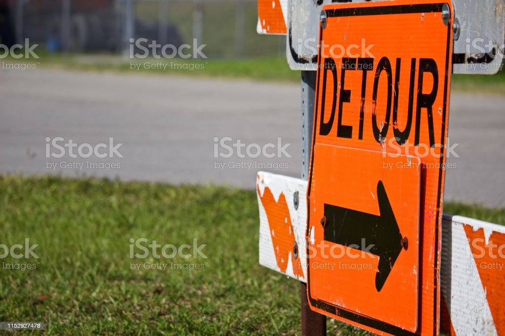 Detour sign pointing right on orange and white striped road...