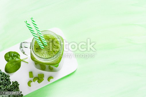 High angle view of a glass filled with green detox drink surrounded by green vegetables shot on green background. The composition is at the left of an horizontal frame leaving a useful copy space for text and/or logo. Predominant color is green. DSRL studio photo taken with Canon EOS 5D Mk II and Canon EF 100mm f/2.8L Macro IS USM.
