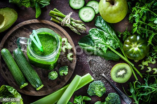 Top view of a rustic table filled with green fruits and vegetables for a perfect detox diet. At the left of an horizontal frame is a glass with fresh green smoothie and a large variety of fruits and vegetables are all around it. Predominant color is green. Low key DSRL studio photo taken with Canon EOS 5D Mk II and Canon EF 100mm f/2.8L Macro IS USM