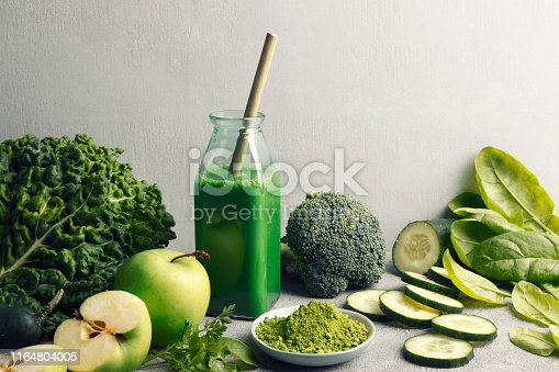 Smoothie and bamboo straw with green fruits, vegetables and matcha.