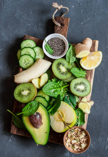 Detox green vegetables and fruits on a wooden board. Concept of a healthy, diet food. Smoothie ingredients.Top view stock photo