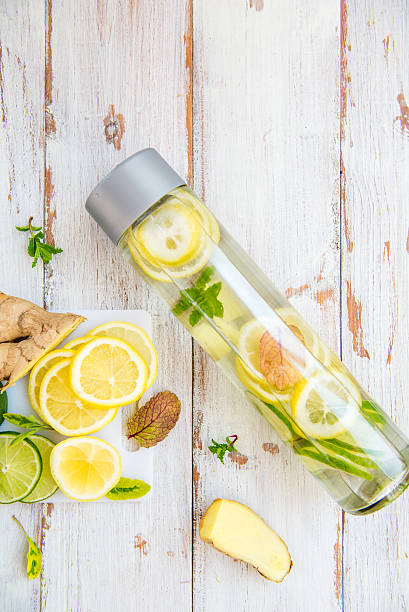 detox infused water with lemon, lime, ginger lemonade - ingwerwasser zubereiten stock-fotos und bilder