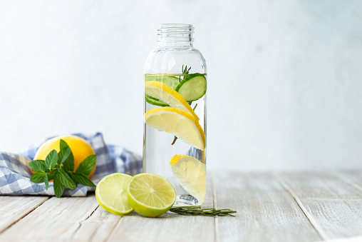 Bottle of infused water on white wood with a slice of lemon , cucumber and rosemary leaf in it.