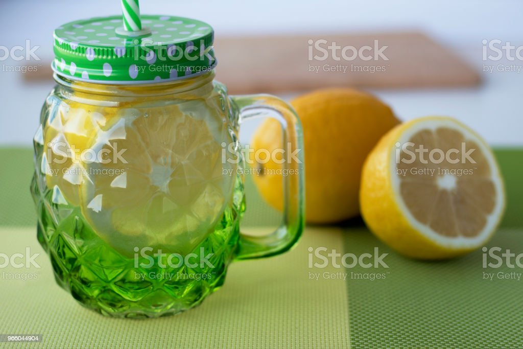 Detox water. Infused water with lemon. Beautiful glass mug with a lid and a drinking tube. - Royalty-free Backgrounds Stock Photo