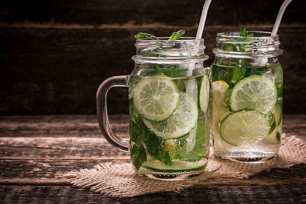 detox water with a lemon, lime and mint on  wood stock photo