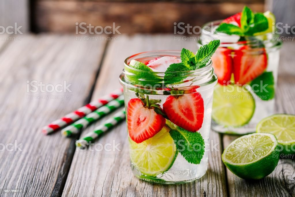 Detox water with  strawberry, lime and mint. Ice cold summer cocktail or lemonade in glass mason jar stock photo