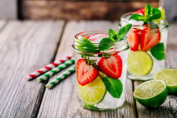 desintoxicação de água com morango, limão e hortelã. gelo frio verão coquetel ou limonada no pote de vidro - tea drinks - fotografias e filmes do acervo