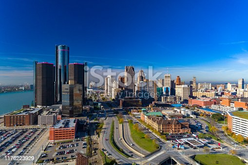 An aerial view of Downtown Detroit skyline with a mostly clear blue sky, and a highway in the foreground and the Detroit river to the left.