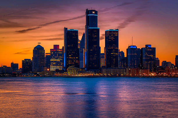 Detroit Skyline at Golden Hour View of Detroit from Windsor, Ontario during a golden sunset. detroit michigan stock pictures, royalty-free photos & images