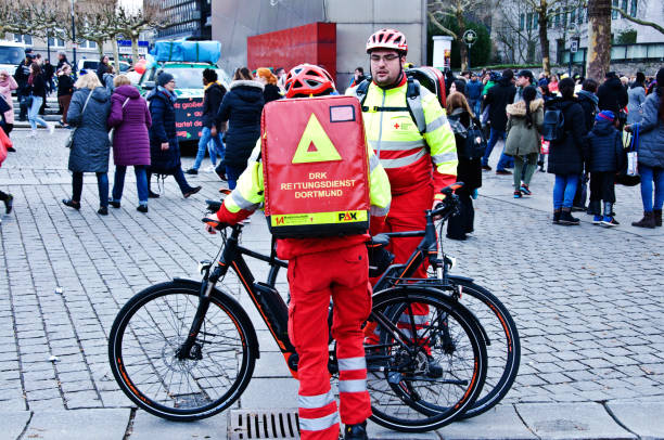 deutsches rotes cross: german first responders and paramedics (red cross) with their bicycles at the 2019 dortmunder rosenmontag (rose monday parade) in germany - first responders стоковые фото и изображения
