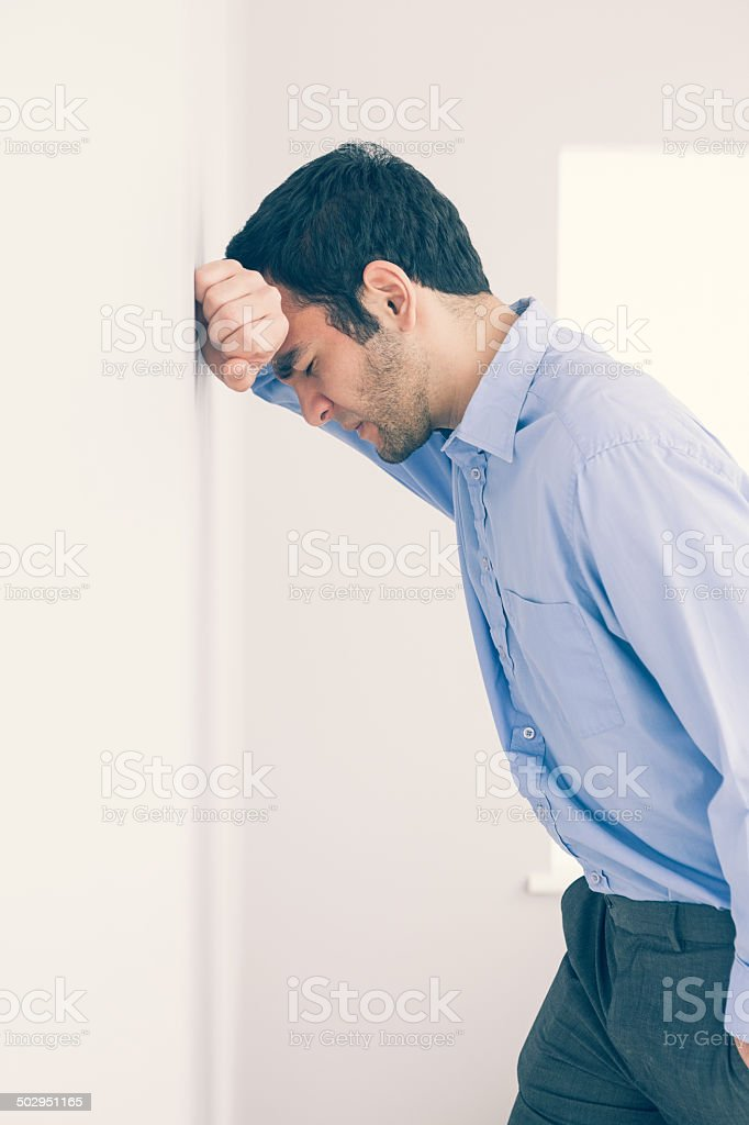 Devastated man leaning his head against a wall stock photo