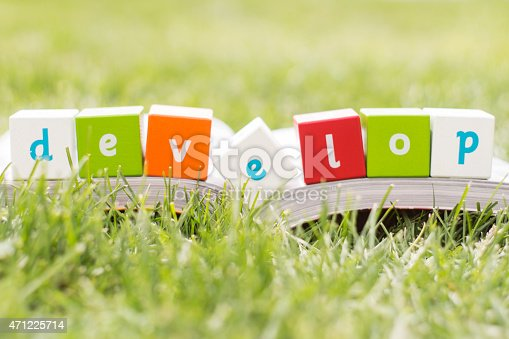 Develop , word with book on grass
