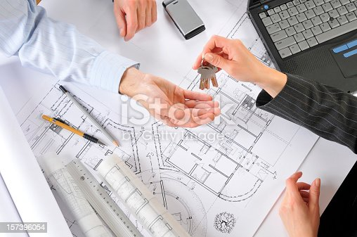 istock Developer giving new house keys to the client, building plans 157396054