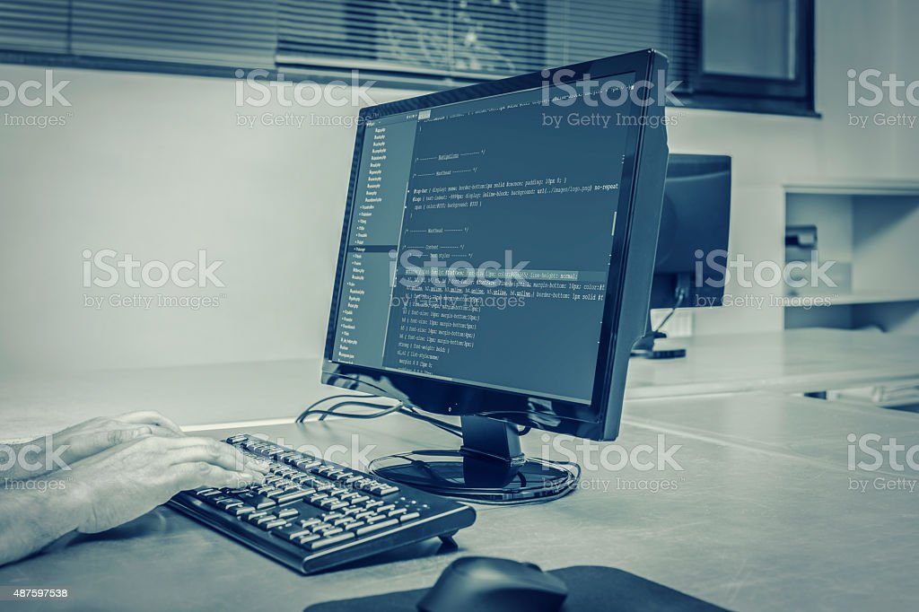 developer working backend source codes on office computer stock photo
