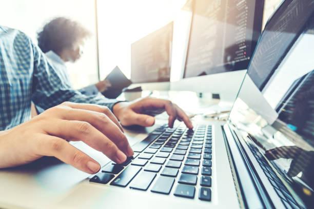 プログラマのチーム開発ウェブサイトのデザインを開発し、符号化ソフトウェア会社のオフィスで働く - エンジニア ストックフォトと画像