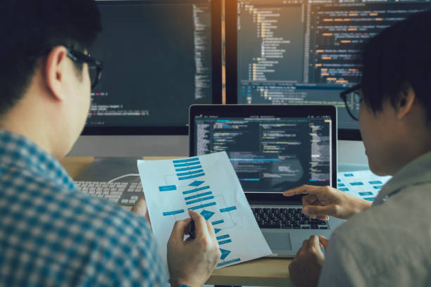 Developing programming and coding technologies working in a software engineers developing applications together in office. stock photo