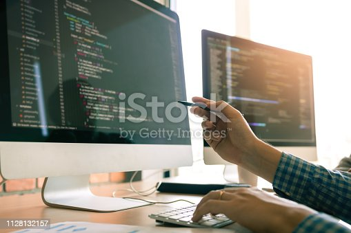 istock Developing programming working in a software engineers code tech applications on desk in office room. 1128132157