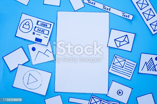 1182469817 istock photo Developing wireframe sketch layout design mockup on smartphone,tablet screen. 1133306639