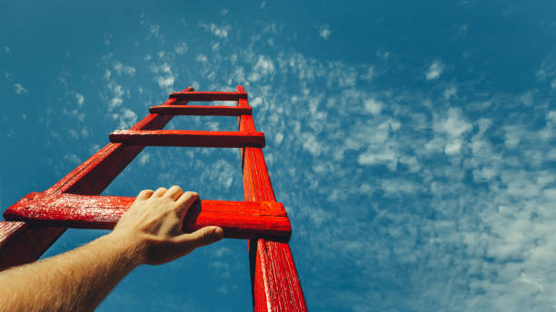 Development Attainment Motivation Career Growth Concept. Mans Hand Reaching For Red Ladder Leading To A Blue Sky A male hand holds onto the crossbar of a red wooden staircase leading to the blue sky high up stock pictures, royalty-free photos & images