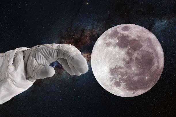 desarrollo de la luna, concepto. Mano del astronauta astronauta tira de su mano a la luna. - foto de stock