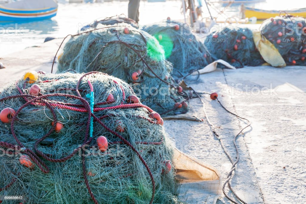 Devices for fishing. Fishing nets lie on the dock. Early morning in Marsaxlokk, Malta. stock photo