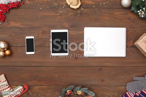 New year theme smartphone digital tablet and laptop isolated on wooden table top view close-up