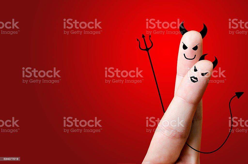 Devil finger couple in love; painted smiley and hugging stock photo