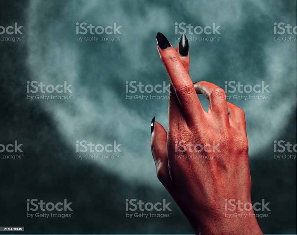Devil hand with gesture cross fingers at midnight stock photo
