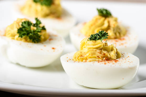 Deviled eggs garnished with parsley and paprika stock photo