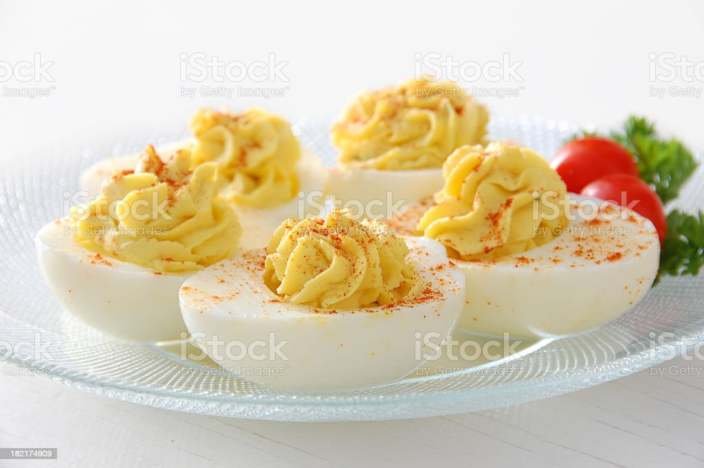 Deviled eggs served on clear plate with grape tomatoes stock photo