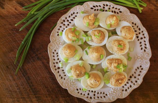 deviled eiern mit kabeljau leber mit lauch auf weißen teller. rustikaler holztisch - gefüllte eier stock-fotos und bilder