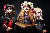 Ominous portrait of three little girls with fearful make-up holding burning candles and open old book