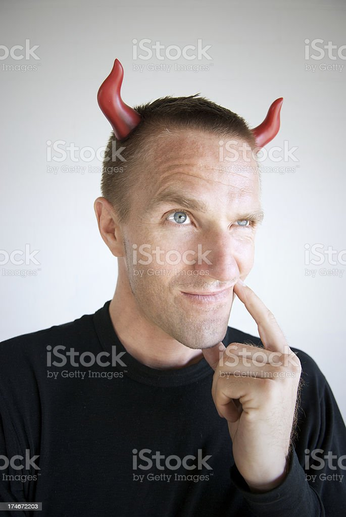 Devilish Man in Black Looks Up with Mischievous Smirk royalty-free stock photo